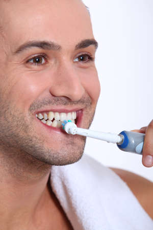 dentalcare: Closeup of young man brushing his teeth Stock Photo