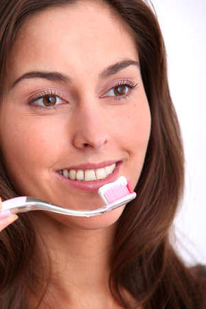 toothcare: Closeup of beautiful woman brushing her teeth Stock Photo