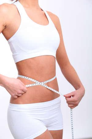 Closeup of tape measure around woman waist photo