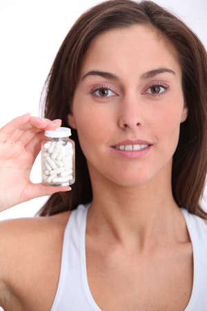 Closeup of woman holding bottle of pills photo