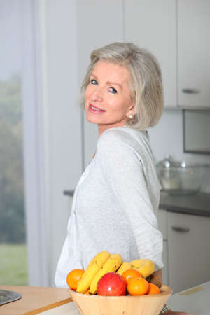 Senior woman standing in kitchen Stock Photo - 8400906