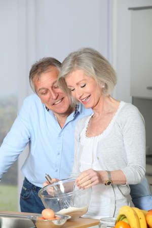 Senior couple in kitchen baking cake photo