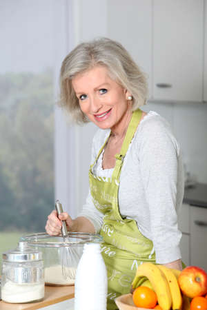 Closeup of smiling senior woman baking in kitchen photo