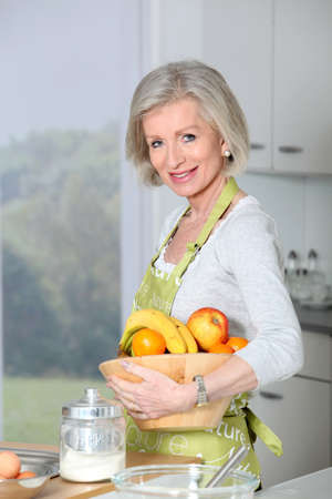 Smiling senior woman in kitchen Stock Photo - 8400886