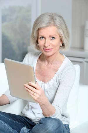 electronic pad: Closeup of senior woman sitting on sofa with electronic pad Stock Photo