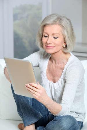 senior ordinateur: Gros plan des haute femme assise sur le canap� avec tampon �lectronique