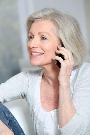 Happy senior woman talking on mobile phone photo