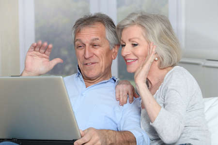 Senior couple waving at web camera Stock Photo - 8400852