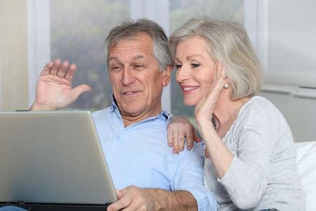 Senior couple waving at web camera Stock Photo - 8400852