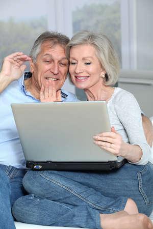 Senior couple waving at web camera photo