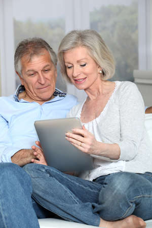 Senior couple surfing on internet with electronic tablet photo