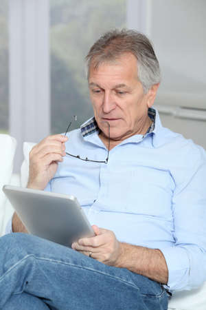 Senior man sitting in sofa with electronic tablet Stock Photo - 8401975