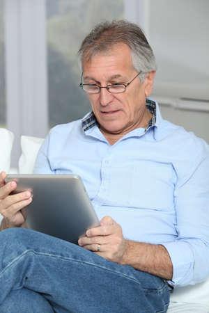 Senior hombre sentado en el sofá con tableta electrónica