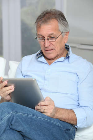 senior reading: Senior man zit in sofa met elektronische tablet