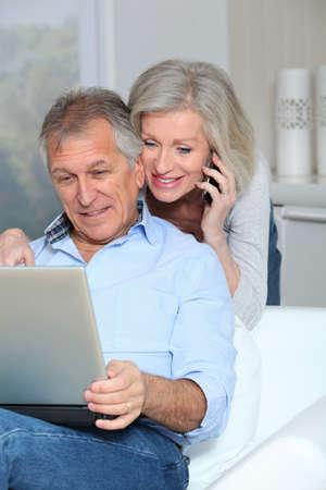 senior ordinateur: Couple sup�rieurs � la maison surf sur internet Banque d'images