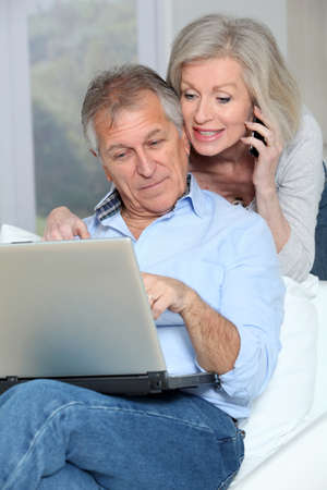 Senior couple at home surfing on internet photo