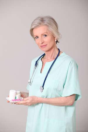 Closeup of senior nurse standing on white background photo