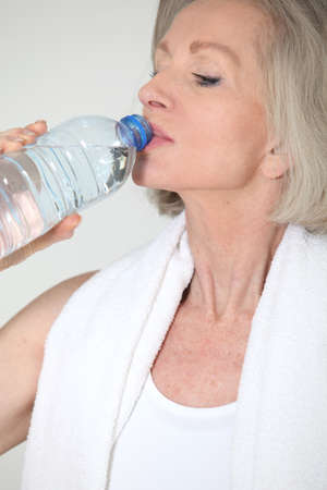 Portrait of senior woman with bottle of water after exercising photo