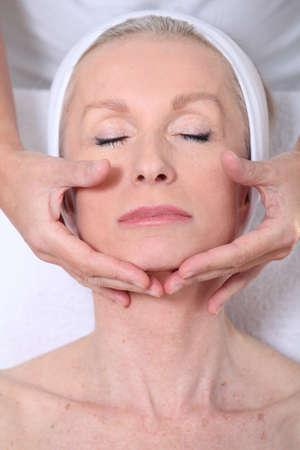 hairband: Closeup of senior woman having a face massage