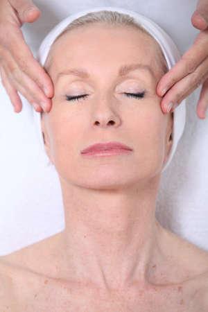 Closeup of senior woman having a face massage photo