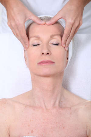 senior health: Closeup of senior woman having a face massage