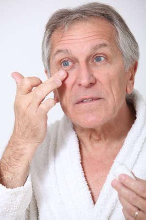 concealer: Senior uomo mettendo concealer intorno gli occhi