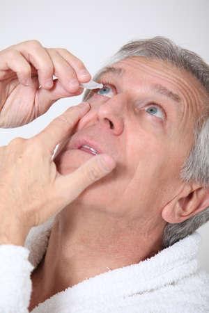 lentes de contacto: Hombre Senior poner gotas para los ojos Foto de archivo