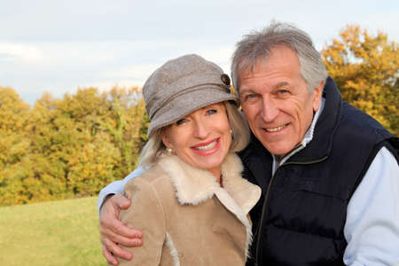 Happy senior couple embracing each other in countryside photo
