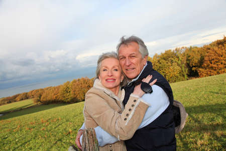 60 years old: Happy senior couple embracing each other in countryside