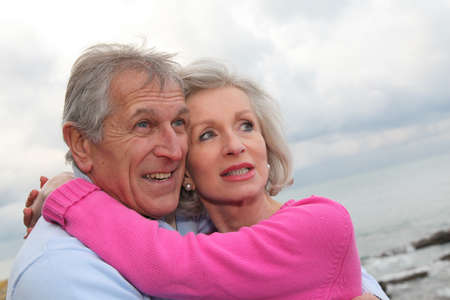 60 years old: Happy senior couple embracing each other by the sea Stock Photo