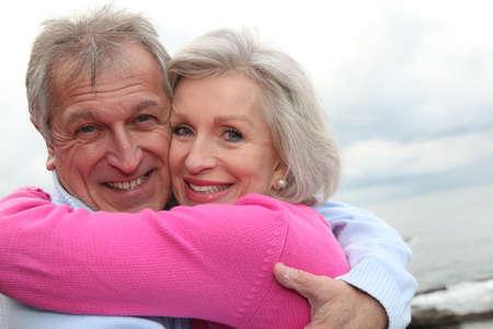 pareja de esposos: Feliz pareja senior abarca unos a otros por el mar
