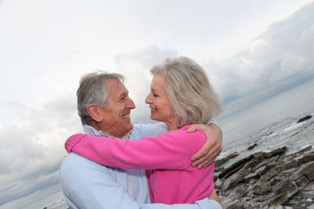Happy senior couple embracing each other by the sea photo