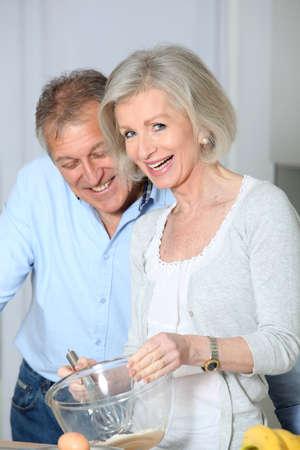 baking cake: Senior couple in kitchen baking cake Stock Photo