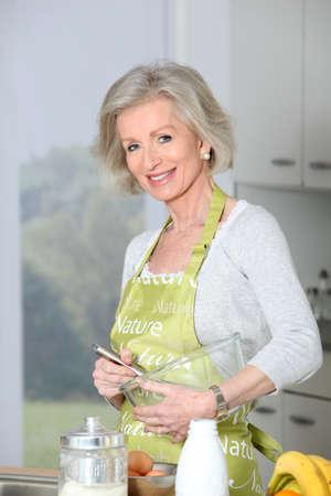 home baking: Closeup of smiling senior woman baking in kitchen