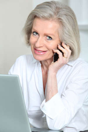 telephone saleswoman: Senior businesswoman in the office talking on the phone