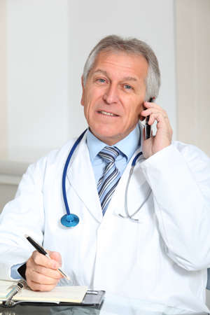 medicalcare: Closeup of doctor talking on the phone in the office