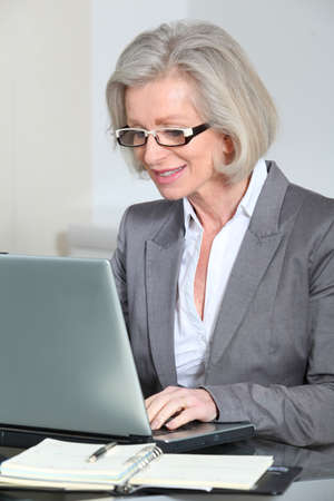 Senior businesswoman with eyeglasses working in the office photo