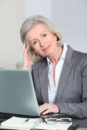 desk clerk: Senior businesswoman working in the office