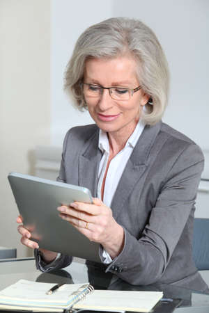 android tablet: Portrait of senior businesswoman in office Stock Photo