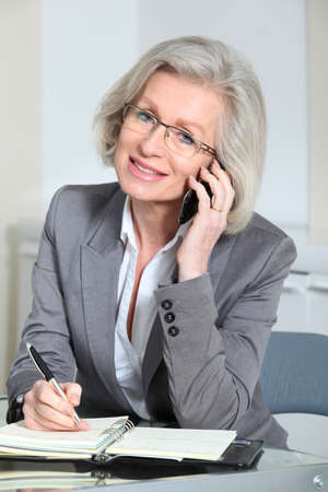 Portrait of senior businesswoman talking on the phone in office photo