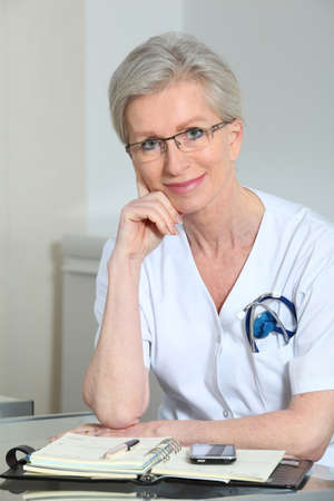 Portrait of smiling mature nurse in office photo