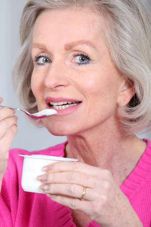 Portrait of senior woman eating yoghurt photo