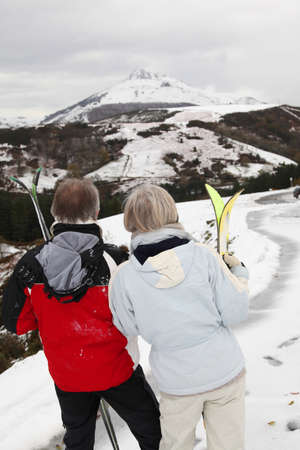 Senior couple at ski resortlooking at the mountain photo