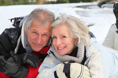 60s adult: Senior couple having fun at ski resort