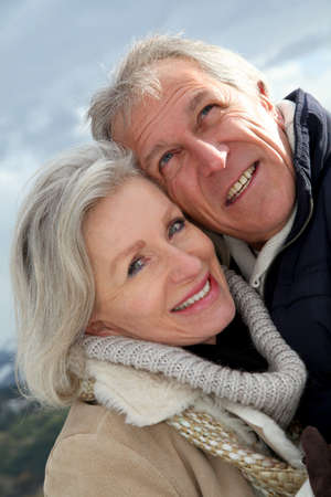winter jacket: Portrait of happy senior couple at the mountain Stock Photo