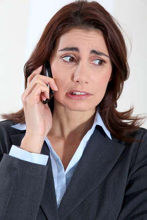 preoccupied: Businesswoman on the phone with preoccupied look
