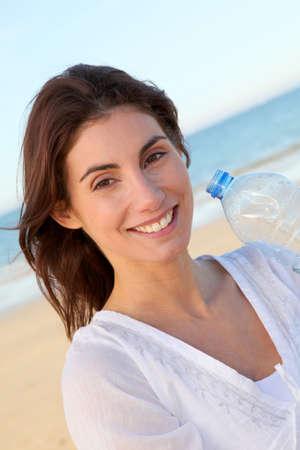 Portrait of woman drinking water from bottle photo