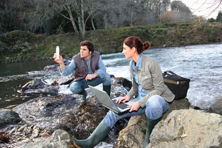 environmental science: Biologists testing water of natural river