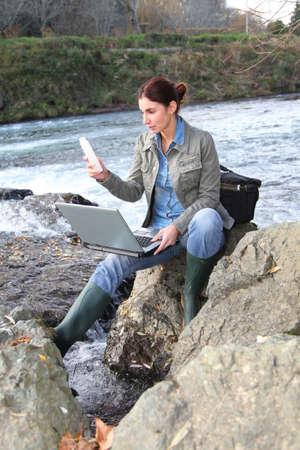 water contamination: Mujer cient�fico pruebas de calidad del agua en el r�o