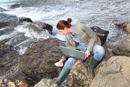 Woman scientist testing quality of water in river photo